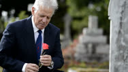 Stock Video Footage of Sad elderly man lays flower on grave, looks at headstone