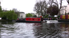 Barge turning and moving along a canal in London - stock footage