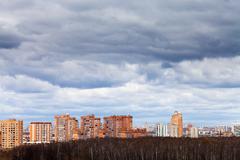 rainy clouds under urban houses - stock photo