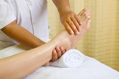 reflexology foot massage, spa foot treatment - stock photo