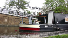 Barge on canal in London with man jogging past Stock Footage