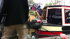 Regents canal in London with canal boats and people walking past Stock Footage