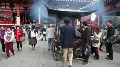 People burning aromatic sticks in Incense burner, Asakusa, Japan - stock footage