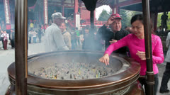 People burning aromatic sticks in the incense burner, Japan - stock footage