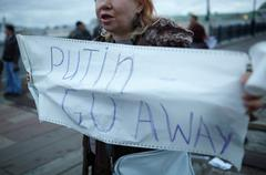 Woman holds a placard Putin Go Away. - stock photo