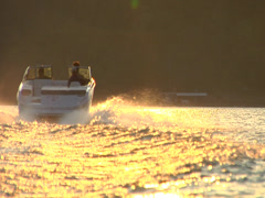 Ski boat going off into sunset Stock Footage