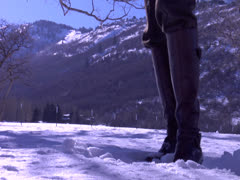 A girl making snowballs to throw at someone only to flirt close shot - stock footage