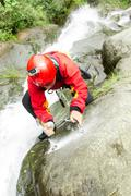 Instructor Drilling Holes For A New Canyoning Route In Chama Waterfall Ecuador Stock Photos