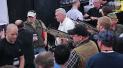 Men looking at guns at Nation Rifle Association Convention (HD)k - stock footage