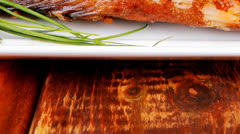 Served main course on wood: fried seabass Stock Footage