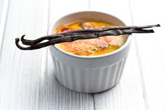 creme brulee in ceramic bowl with vanilla pod - stock photo