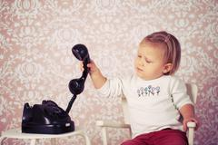 little baby with old vintage phone - stock photo