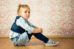 Beautiful little girl sitting on floor Stock Photos