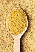 bulgur wheat in wooden spoon - stock photo