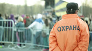 Back of a security guard in front of blurred crowd Stock Footage