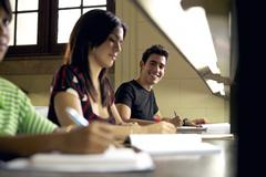 happy student studying and writing, portrait of hispanic young man - stock photo