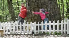 Mom and daughter are trying to clasp hands  oak trunk - stock footage
