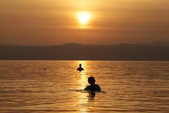 Woman & man silhouette in sea - stock photo