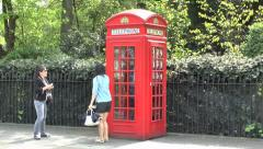 Tourists pose beside a London red telephone box, London, UK. Stock Footage