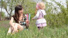 Mother with baby blows soap bubbles. Dolly shoot. - stock footage