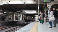 JR train of Yamanote line arriving to platform with passengers, Tokyo, Japan Stock Footage