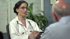 Female doctor consulting with senior patient Stock Footage