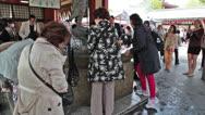 Tourists washing hands with ladles,  Senso-ji, Tokyo, Japan Stock Footage