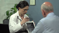 Female doctor showing patient's x-ray with tablet Stock Footage