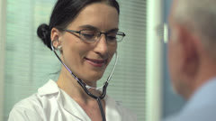 Female doctor listening senior patient's heart rate Stock Footage