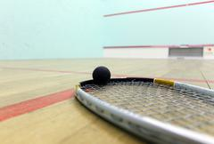 Squash court and racket with ball Stock Photos