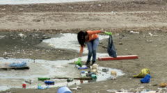 Young beautiful woman trying to clean dirty beach Stock Footage