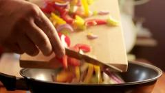 Sliding vegetables into pan on stove, cooking in kitchen - stock footage
