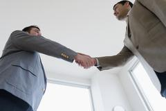 Businessmen shaking hands in office Stock Photos