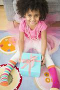 African American girl opening present in living room Stock Photos