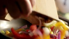 Adding vegetables to pan on stove, cooking in kitchen Stock Footage
