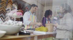 Happy mixed ethnicity store assistants take payment from a customer Stock Footage