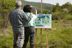 Caucasian couple visualizing house in rural landscape Stock Photos