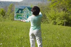 Caucasian woman visualizing house in rural landscape Stock Photos