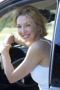 Caucasian woman smiling in driver's seat - stock photo