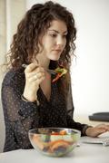 Caucasian businesswoman eating salad at desk Stock Photos