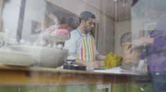 Happy friendly store assistant serves a customer in his shop  Stock Footage