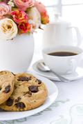 Chocolate chip cookie  on white plate with black coffee and flower Stock Photos