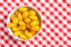 Yellow tomatoes on picnic tablecloth Stock Photos