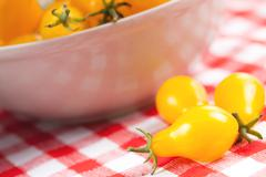 Stock Photo of yellow tomatoes on picnic tablecloth