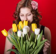 girl with a bouquet of tulips on red background - stock photo