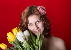 beautiful green-eyed girl with a bouquet of tulips - stock photo