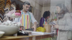 Happy mixed ethnicity store assistants take payment from a customer - stock footage