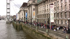 Crowds outside the County hall on the banks of the Thames river in London Stock Footage