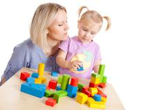 Little girl and her mother playing with toy blocks Stock Photos