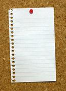 Small page from a notepad stuck to a cork noticeboard. Stock Photos